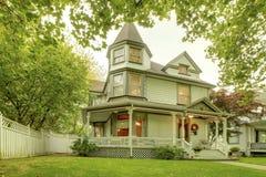 Stort hem med den trevliga främre gården, farstubron, vita räcke och gångbanan Royaltyfria Bilder