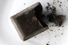 Stort huggit av stycke av chokladlögner på en vit keramisk platta royaltyfri fotografi