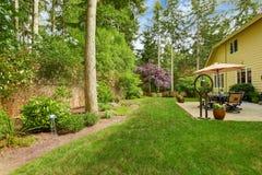 Stort hus med trädgårduteplatsen och landskap Fotografering för Bildbyråer