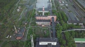 Stort industriellt gods med arbetande fabriksskorsten och gamla röda byggnader nära flyg- sikt för skog stock video