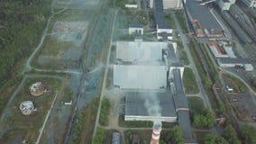 Stort industriellt gods med arbetande fabriksskorsten och gamla röda byggnader nära flyg- sikt för skog arkivfilmer