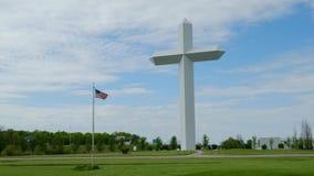 Stort kors i Effingham, Illinois mot en blå himmel med amerikanska flagganflyget lager videofilmer
