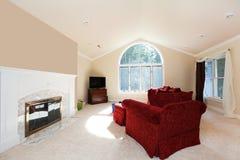 Stort ljust vardagsrum med röd sofa- och vitspis. Arkivfoton