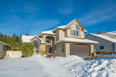 Stort lyxigt hus med den främre gården i snö Arkivbilder