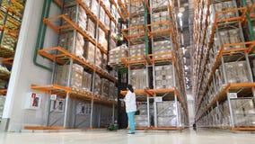 Stort modernt lager med gaffeltruckar Warehouse arbetaren som tar packen i hyllan i ett stort lager i ett stort Royaltyfri Foto