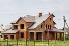 Stort modernt två-storied inte avslutade det nya huset för tegelstenfamiljstugan med det branta bruna överlappade taket, garage,  royaltyfria bilder