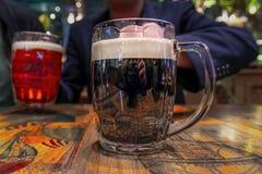 Stort råna av mörkt öl med vitt skum på tappningträtabellen royaltyfri fotografi