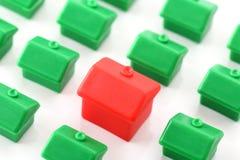 Stort rött hus som står ut från små gröna hus Arkivfoton