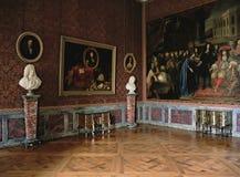 Stort rött rum med målningar och marmorstaty på den Versailles slotten, Frankrike Royaltyfria Bilder