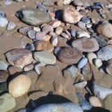 Stort randigt vaggar sten- & sandbakgrundsramen på stranden Arkivbilder