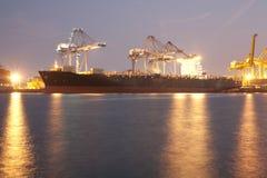 Stort skepp i hamn genom att använda kranar som laddar behållare i nattetid Arkivfoto