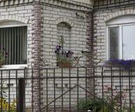 Stort specialtillverkat lyxigt hus med den utmärkt landskap främre gården och körbanan som parkera bilen i garage i förorterna av royaltyfri bild