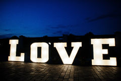 Stort stort bokstavsord FÖRÄLSKELSE med ljus inom på nattbröllopce Fotografering för Bildbyråer