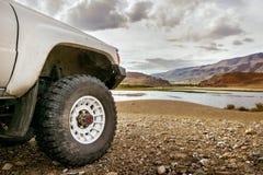 Stort SUV bilhjul på bakgrunden av sjön Arkivfoton