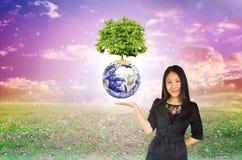 Stort träd på jord ovanför att framlägga handen av Asien kvinnor på fantasi Arkivfoton