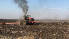 Stort traktorarbete i fältet, traktor som plogar fältet stock video