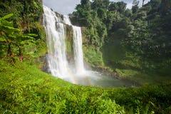 Stort vattenfalllandskap med en regnbåge Tad Yuang den dramatiska vattenfallet tappar 40 metrar över en klippa och en tropisk sko arkivbild