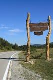Stort wood tecken vid vägen på berg Royaltyfri Bild