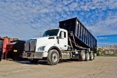 Stortplaatsvrachtwagen die een bouwcontainer plaatsen Royalty-vrije Stock Fotografie