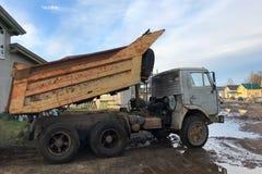 Stortplaatsvrachtwagen met een opgeheven lichaam op een modderige weg royalty-vrije stock fotografie