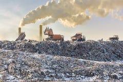 Stortplaatsvrachtwagens die huisvuil over enorme stortplaats leegmaken Rokende industriële stapels op achtergrond ecologische cri stock afbeelding