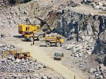 Stortplaatsvrachtwagens en graafwerktuigen in de granietsteengroeve Stock Foto's