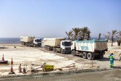 Stortplaatsvrachtwagens op een bouwwerf langs de weg tussen Doubai en Sharjah Stock Foto's