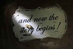 The story begins. Wedding rings and now the story begins written on wooden plate. love and friendship stock photography
