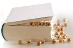 Story - message with wooden letter blocks in a book. Story - message for creative writing spelled with wooden letter blocks between pages of a white book Stock Image