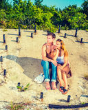 Story Teller. Guy wearing jeans, barefoot, half naked, girl dressing in skirt, tank top,  sunglasses on head, a young couple is sitting on the concrete slope Stock Photo