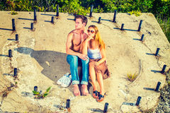 Story Teller. Guy wearing jeans, barefoot, half naked, girl dressing in skirt, tank top,  sunglasses, a young couple is sitting on the concrete slope with Stock Photo
