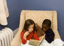 Story Time 2. Two small children reading together in a big chair.  Diversity Royalty Free Stock Image