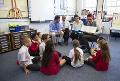 Story Time in a Classroom. A group of children sit on the floor cross legged, listening to a group of teachers read a story stock photo