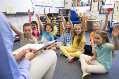 Story Time in a Classroom. A group of children sit on the floor cross legged, listening to the teacher. They all have their hands raised in the air to answer a royalty free stock images