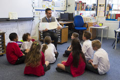 Story Time in a Classroom. A group of children sit on the floor cross legged, listening to the teacher read a story royalty free stock photography