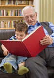 Story time with grandpa. Grandfather reading a story to his grandchild Stock Images