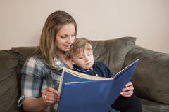 Story Time. A young boy quietly listens as his mother reads to him stock image