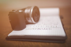 Storyboard and camera in sepia. Portrait of notepad with storyboard and digital camera on it in sepia Royalty Free Stock Image