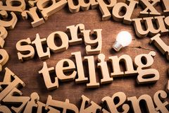 Storytelling Idea. Storytelling word in scattered wood letters with glowing light bulb royalty free stock photo