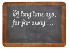Storytelling opening phrase. A long time ago, far, far away - a phrase for opening oral narratives, story or fairytale on a vintage blackboard, copy space below Stock Photography