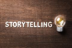 Storytelling Text and Bulb. Storytelling word with glowing light bulb on wood texture stock image