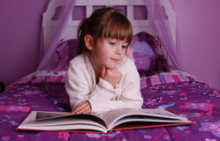 Storytime. A cute young girl lying on her bed reading a book Royalty Free Stock Images