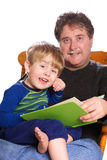 Storytime. A father reads a bedtime story to his son stock images