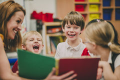 Storytime At School. Teacher is sitting in the classroom with her primary school students, reading a story to them royalty free stock photo