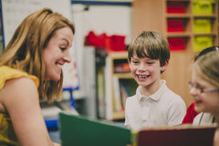 Storytime At School. Teacher is sitting in the classroom with her primary school students, reading a story to them royalty free stock image