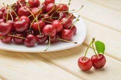 Stos świeże wiśnie w białym talerzu w pierwszoplanowych dwa jagodach z zielonym liściem, tabela drewna obrazy stock