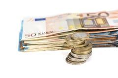 Stos banknoty wystawia rachunek euro i stos monety Zdjęcia Stock