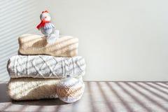 Stos ciepli trykotowi pulowery z bożymi narodzeniami ornamentuje bałwanu na drewnianym stole na lekkim tle i bawi się fotografia stock