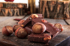 Stos czekolada kawałki z hazelnuts na drewnianym tle Zdjęcie Stock