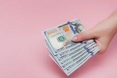 Stos dolarowi s banknoty w ?e?skiej r?ce na r??owym tle zdjęcia stock